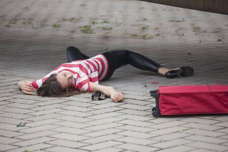 vermoord: onbewuste vrouw liggend op asfaltweg Stockfoto