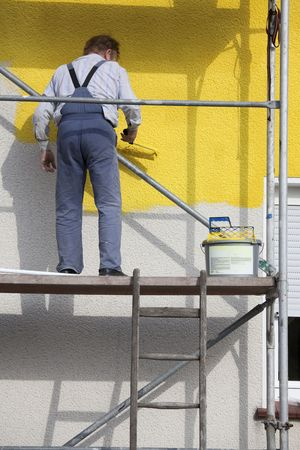man on a scaffold painting house with roller photo