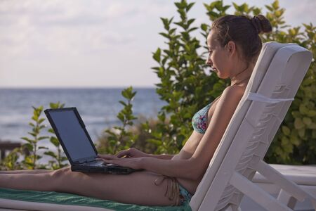 woman in bikinis with laptop in Chaise photo