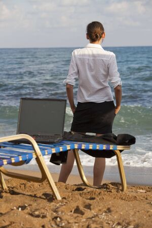 business woman standing at the beach, laptop on the chaise photo