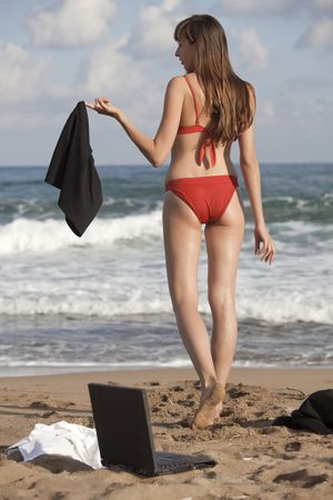 woman undresses her business skirt on the beach photo