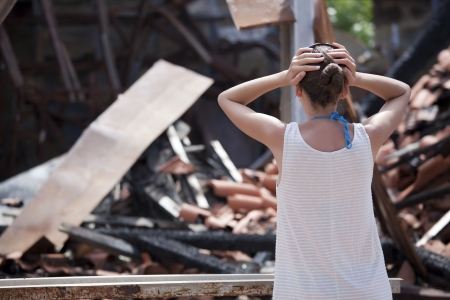 front of house: woman standing in front of burned out house and holding her head with both hands