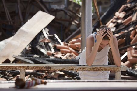 fire damage: sad woman standing in front of destroyed house