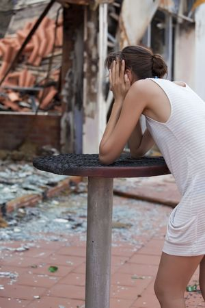burned out: pained woman stands in front of burned out house