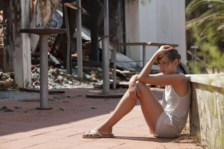 burned out: sad woman sitting in front of burned out house