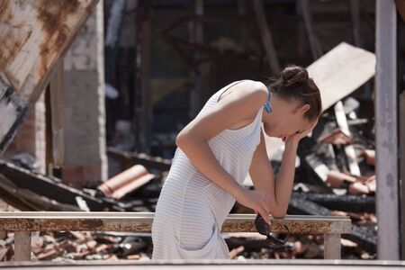 burned out: sad woman standing in front of burned out house