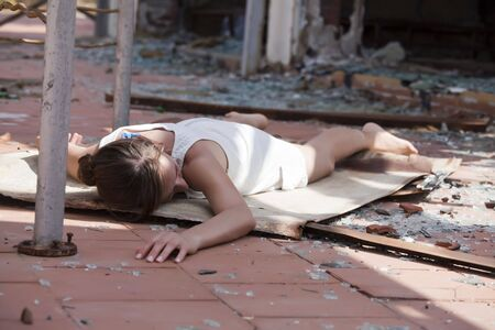 model acting a unconscious woman on the street after house explosion Stock Photo