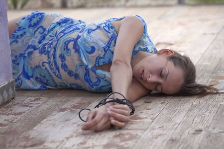 tied woman: model playing a unconscious kidnapped woman Stock Photo