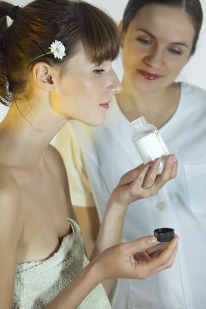 smells: woman smells cosmetic product in a wellness salon Stock Photo