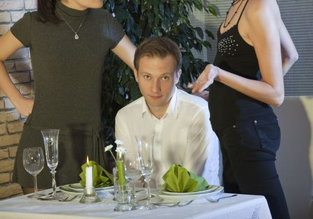 two women discussing over man in a restaurant Stock Photo - 5690247
