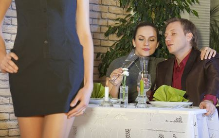 dining out: man looking at a nice girl passing by while dining out with his girlfriend in restaurant