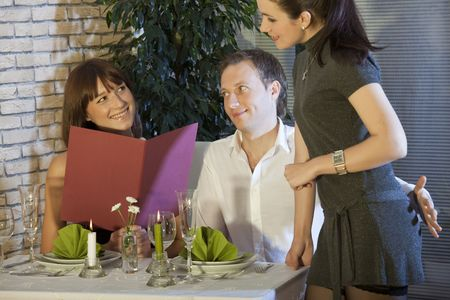 man holding his hand on waitress buttocks in a restaurant photo