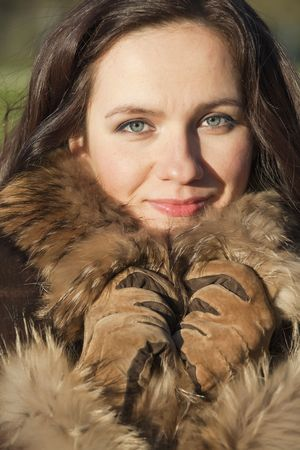 portrait of fashion woman in fur coat posing outdoor photo