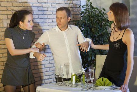 dos mujeres peleando por el hombre en un restaurante Foto de archivo - 5773723