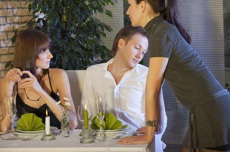 unfaithful: man flirting with waitress in a restaurant Stock Photo