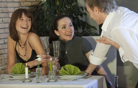 arousing: man flirting with two women in a restaurant