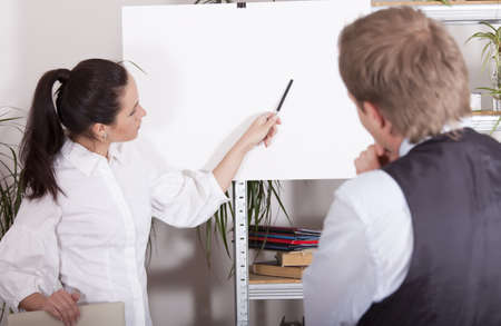 woman pointing with a pen on white billboard in office photo