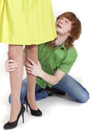 suplicando: hombre llora en las rodillas, manteniendo las piernas de la mujer y pidiendo