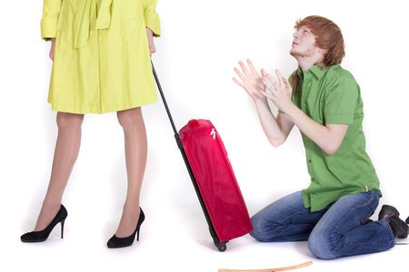 pleading: crying man on knees pleading to woman with luggage Stock Photo