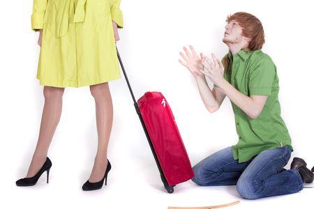 suplicando: hombre llorando en las rodillas rogando a la mujer con el equipaje
