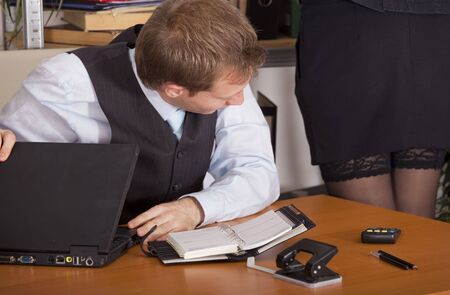 horny businessman looking at woman legs in a office photo