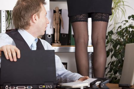 flirt: woman in lingerie standing on a stool - astound man looking at her legs