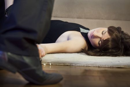 unconscious woman lying on the ground, male shoe in foreground photo
