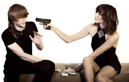young woman threatens man with gun photo