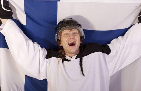happy ice hockey player holding finnish flag photo