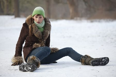 snow falling: woman slips and falls down on snowy road Stock Photo