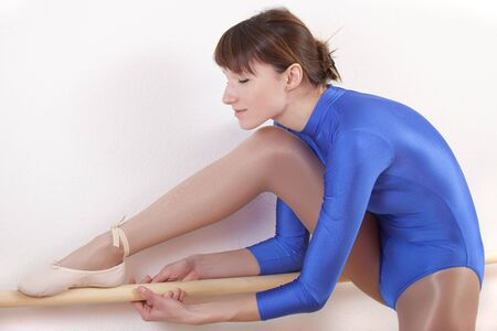 female gymnast in blue leotard stretches at dancing bar Stock Photo