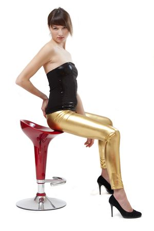 woman in glossy leggings and high heels posing on stool photo