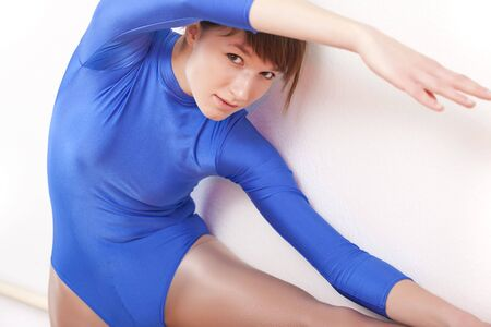 gymnastic woman in blue leotard stretches at dancing bar photo