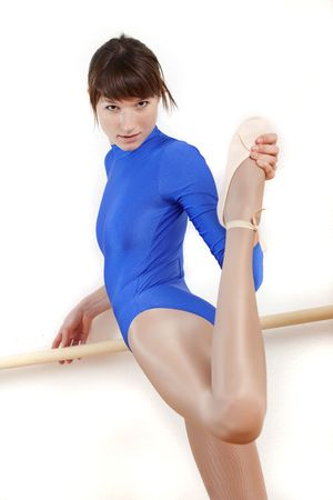 ballet bar: young woman in blue leotard doing stretching exercises
