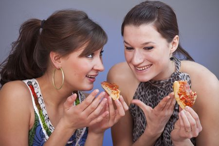 two women talking by lunch holding pizzas photo
