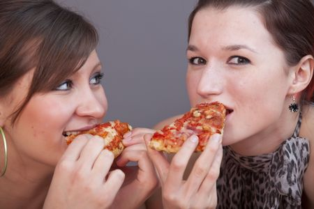 two young women eating pizzas in a studio photo