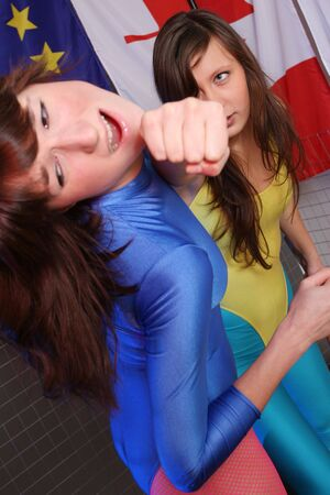 bout: two women in leotards fighting in a cage - studio shot