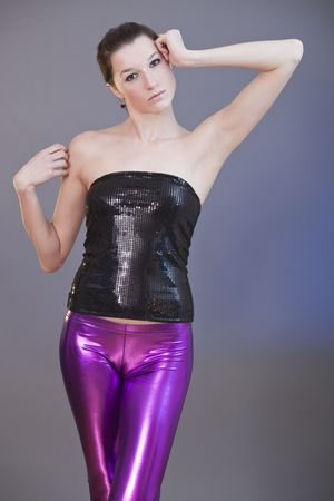 young woman in shiny leggings posing over grey background photo
