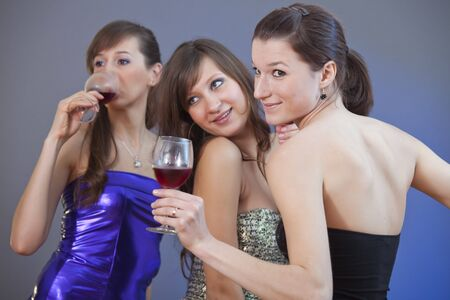 happy women dancing with glasses wine at the disco - studio shot photo