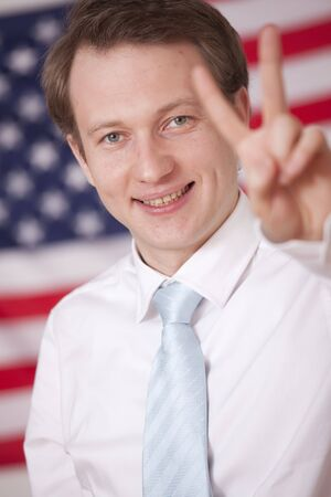 happy businessman showing victory sign over american flag photo