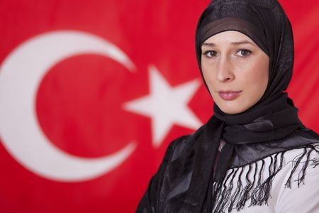 the turkish flag: portrait of muslim woman in front of turkish flag Stock Photo