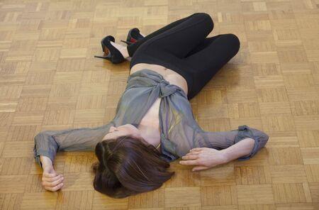 vermoord: onbewuste vrouw liggend op de Bevloering van het hardhout  Stockfoto