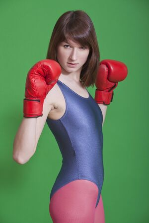 female fighter: young female boxer in gymnastic leotard over green background