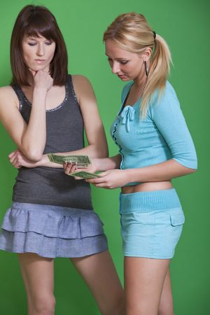 two women counting money on the green background