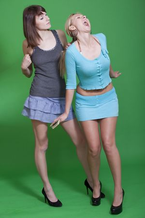 two young women fighting on green background photo