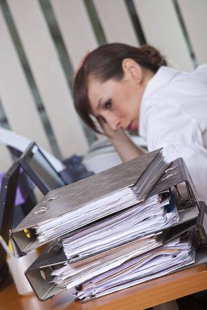 tired businesswoman sitting at her desk with lots of folders - focus on documents in foreground Stock Photo - 6788959