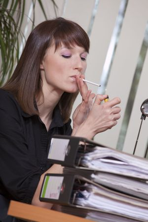 cigarette lighter: young businesswoman smoking cigarette in a office