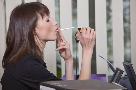 smoker: young business woman smoking cigarette in a office
