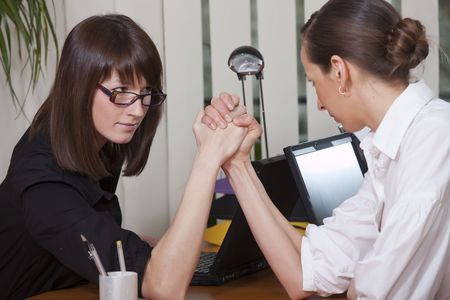 female wrestling: Business arm wrestling between two young women in a office Stock Photo