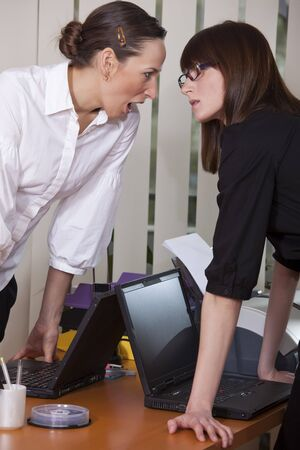two businesswomen screaming each other in a office photo